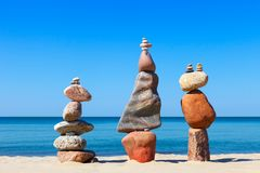 Three Rock zen pyramids of colorful pebbles standing on the beach, on the background of the sea. Concept of balance, harmony and. Meditation stock images