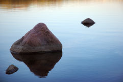 Three rocks. In the water with orange reflection royalty free stock images