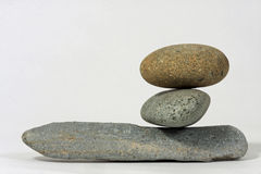 Three rocks balanced. Two rocks balanced on top of a larger rock Stock Images