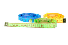 Three rolled measuring tapes of different colors. Isolated on the white background Royalty Free Stock Image