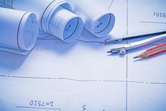Three rolled up blueprints and pencil with compass Stock Photos