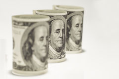 Three rolled up one hundred dollar bills on a white background Royalty Free Stock Photography