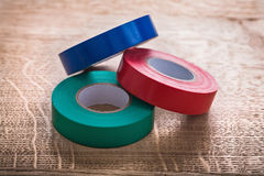 Three rolls of insulating tape on wooden board Stock Photos
