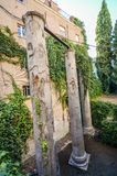 Three roman columns hidden away behind a building on calle Marmoles in Santa Cruz, Seville, Spain.  stock photography