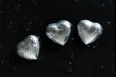 Three romantic chocolate hearts with water drops Stock Photography