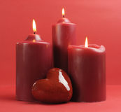 Three romantic red lit candles against a red background. Stock Photo