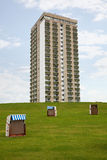 Three roofed wicker beach chairs and a tower block Royalty Free Stock Photos