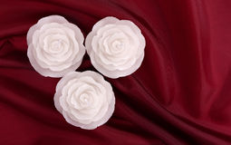 Three rose shaped candles on deep red satin Stock Photo