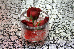 Three rosebuds in vase on pretty patterned tablecloth Royalty Free Stock Photography