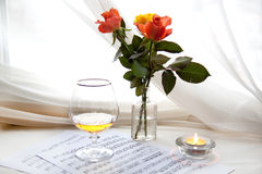 Three roses. Three beautiful roses with music notes, glass and burning candle Stock Image