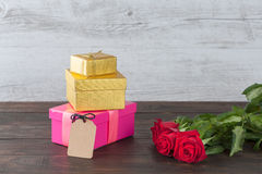 Three roses and gift boxes with tag Stock Photos