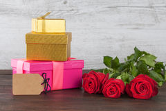 Three roses and gift boxes with tag Royalty Free Stock Images