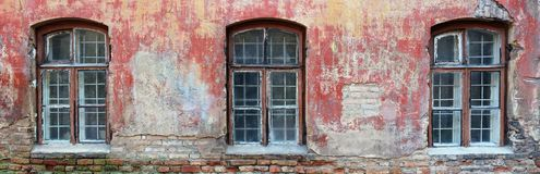Three rotten curved windows in the red wall of a ruined old bric Royalty Free Stock Images