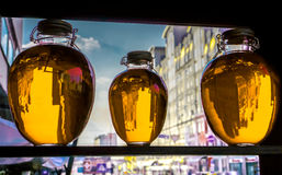 Three round bottles with golden yellow transparent liquid stand on wooden shalved against window Stock Image
