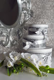 Three round celebration gift boxes with silver ribbon bows on white table and bouquet of orchids. Stacked presents in Stock Photo