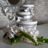 Three round celebration gift boxes with silver ribbon bows on white table and bouquet of orchids. Stacked presents in Stock Image