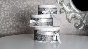 Three round celebration gift boxes with silver ribbon bows on white table. Stack of presents in luxury interior. Stock Image