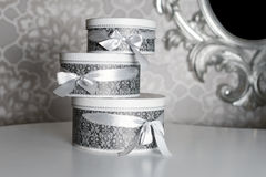 Three round celebration gift boxes with silver ribbon bows on white table. Stack of presents in luxury interior. Royalty Free Stock Image