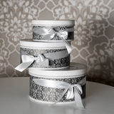 Three round celebration gift boxes with silver ribbon bows on white table. Stack of presents in luxury interior. Stock Photos