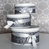 Three round celebration gift boxes with silver ribbon bows on white table. Stack of presents in luxury interior. Royalty Free Stock Photos
