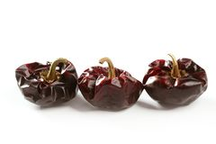 Three round Mediterranean dried dark red peppers Royalty Free Stock Photo