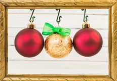Three Christmas globes hanging on photo frame. Three round and shiny Christmas globes hanging on photo frame as happy winter holidays concept Stock Photos