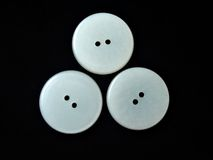 Three round white buttons. Assorted buttons on black background Royalty Free Stock Photos