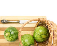 Three round zucchinis in with knife,cutting board,wicker basket Stock Image