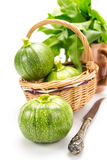 Three round zucchinis in wicker basket with old knife Royalty Free Stock Image