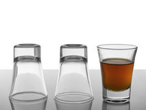 Three in a row. Two empty shots upside down and a third one full of liquor Stock Photography