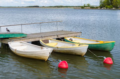 Three rowboats at wooden dock in sea bay Royalty Free Stock Photos