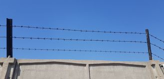 Three rows of barbed wire over gray concrete fence royalty free stock photography