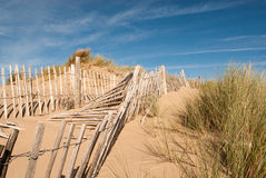 Three rows of broken fence on sand dunes Stock Photos