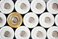 Batteries. Three rows of clean white rechargeable AA batteries with a rusty one symbolizing the problems of recycling an ecology Royalty Free Stock Photos
