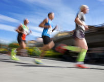 Three running men. Three men in blurred motion in running competition Stock Image
