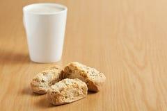 Three rusks with a mug of coffee. Three rusks on a wooden surface with a mug of coffee Royalty Free Stock Photo