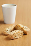 Three rusks with a mug of coffee. Three rusks on a wooden surface with a mug of coffee Stock Image