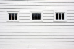 Three Rustic Exterior Windows. On white wood siding. Black vertical glass panes in horizontally oriented window Royalty Free Stock Photos