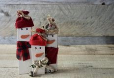 Three rustic snowmen standing on wood surface with a wood background stock image