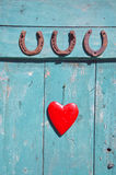 Three  rusty horseshoe luck symbol and red heart on door Stock Photo