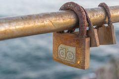 Three rusty Love padlocks over the sea. Look at these tree forgotten locks, plenty of oxide and rust beacuse of the sea water and wind. Help youself with this Stock Photography