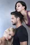Three`s company. Three is company, a men and two women close together Stock Photo
