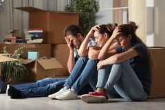 Sad evicted roommates moving home complaining. Three sad evicted roommates moving home complaining sitting on the floor royalty free stock images