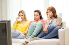 Three sad teenage girl watching tv at home Royalty Free Stock Photos