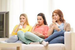 Three sad teenage girl watching tv at home Royalty Free Stock Photography