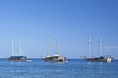 Three sailboaats in sunny weather. Three sailboaats with lowered sails in sunny weather Stock Image