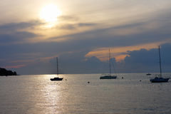 Three sailboats on open sea in a summer at sunset time Royalty Free Stock Photo