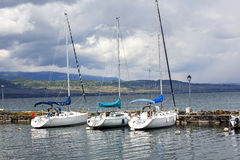 Three sailboats at the port in Yvoire. YVOIRE, FRANCE - MAY 24, 2013: Three sailboats anchored along the stone pier at the port on Lake Geneva. Overcast and no Stock Photo