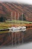 Three sailboats reflected in still water. Three sailboats reflected in still water in the Scottish highlands Royalty Free Stock Photos