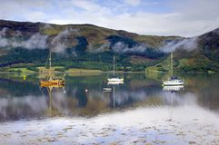 Three sailing boats. On Loch Leven near Ballachulish Glencoe with light clouds drifting by the mountainous backdrop royalty free stock photography